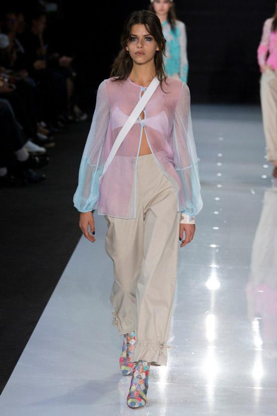 Модель в прозрачной блузке без воротник и светлые брюки от Emporio Armani