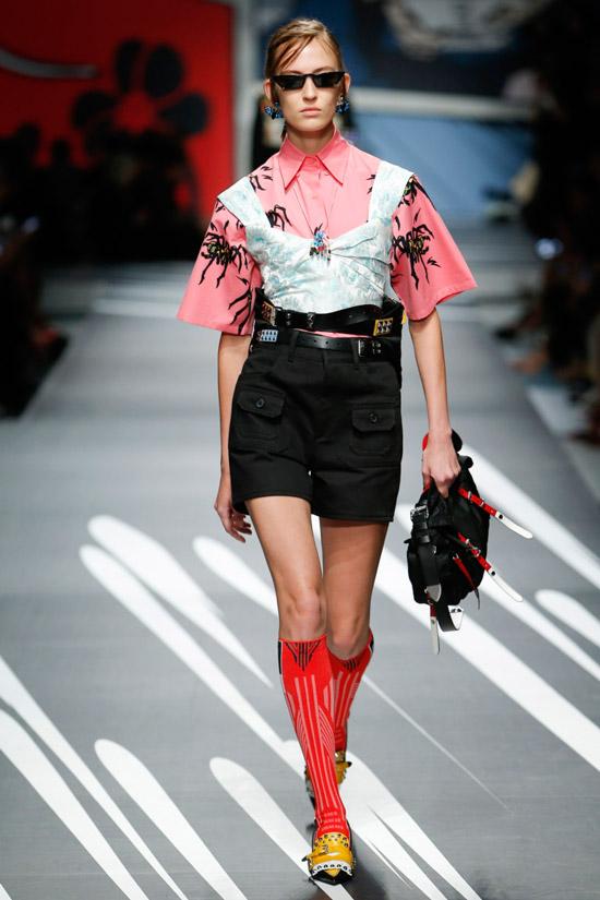 Модель в розовой рубашке с серебристым корсетом и черные шорты с ремнем от Prada