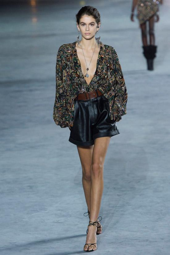 Модель в темной блузке с длинными рукавами и кожаные шорты от Saint Laurent