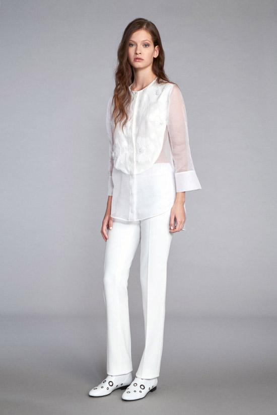 Модель в удлиненной белой блузке без воротника и белых брюках от Kiton