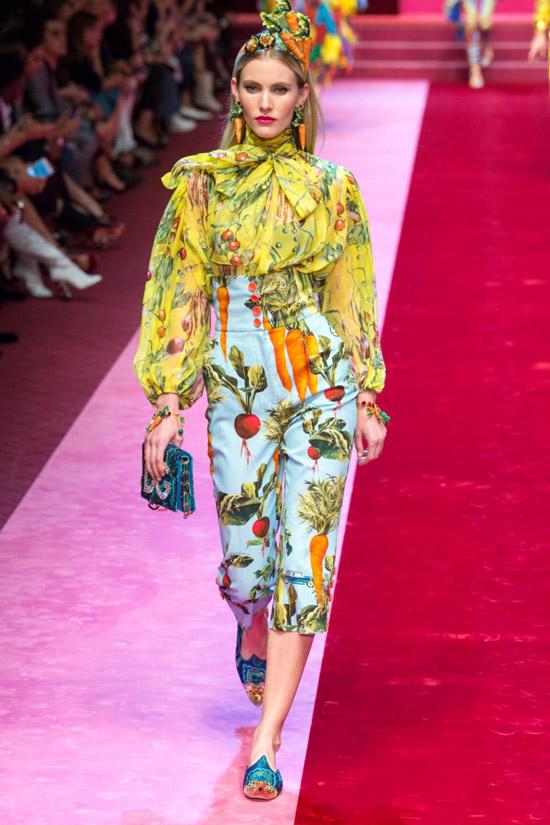 Модель в желтой блузке с принтом и бантом, голубые капри от Dolce & Gabbana