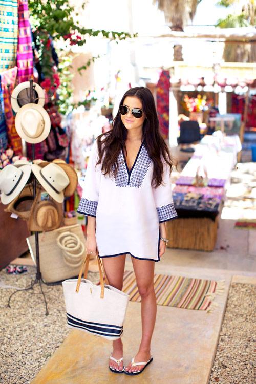 Девушка в белой тунике с черной отделкой, сумка в полоску и шлепки