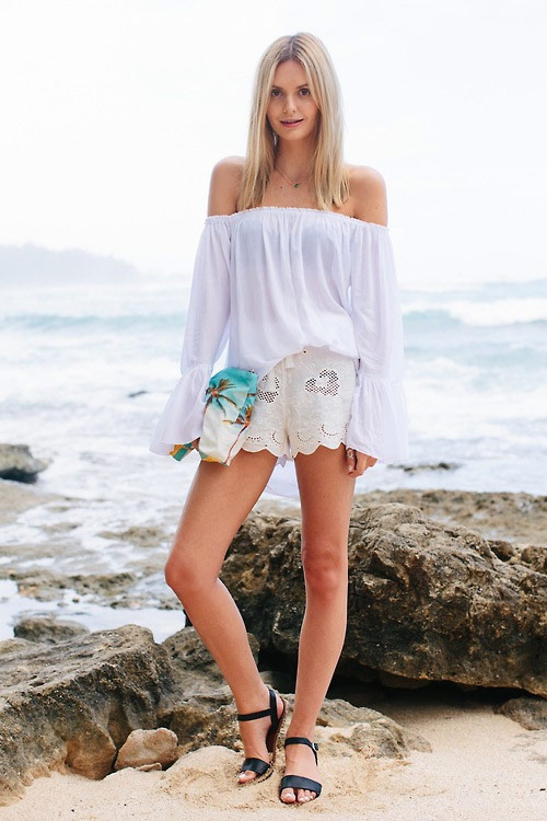 Девушка в белых шортах, блузка с открытыми плечами и черные сандалии