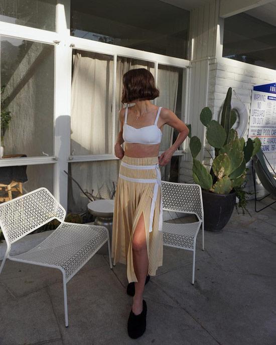Девушка в бежевой юбке миди с разрезом и белый лиф