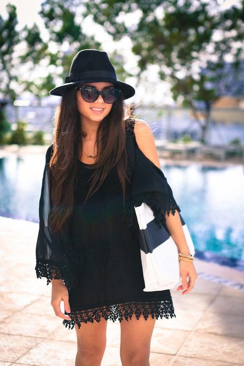 Девушка в черном пляжном платье с открытыми плечами, шляпа и солнцезщитные очки