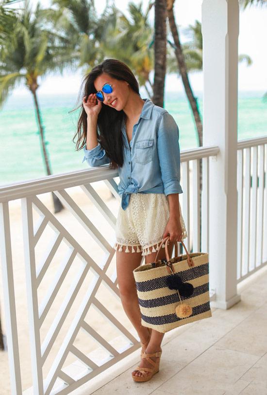 Девушка в голубой джинсовой рубашке, светлые шорты с кисточками и соломенная сумка