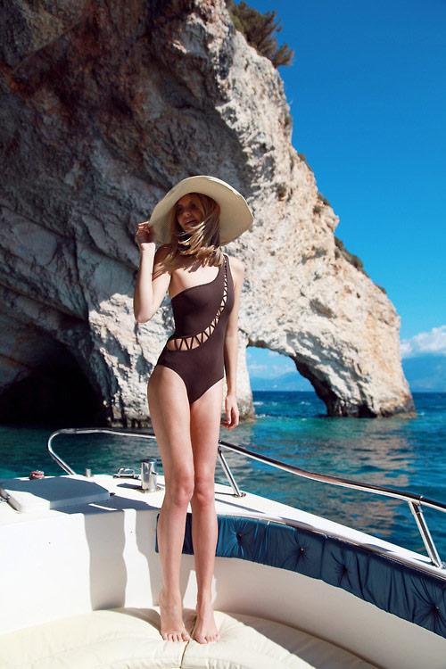 Девушка в коричневом купальнике на одно плечо и большая шляпа