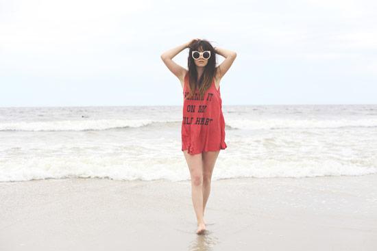Девушка в красной удлиненной майке на пляже
