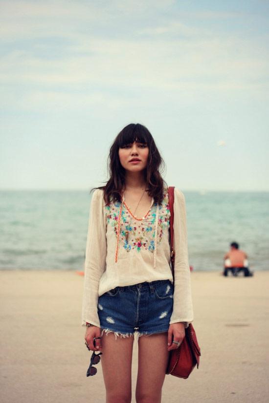 Девушка в тунике с длинным рукавом и джинсовые шорты