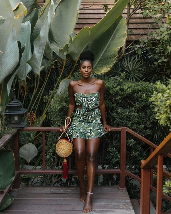 Девушка в зеленой мини юббе и топ с принтом, соломенная сумка