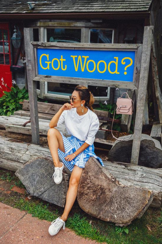 Девушка в белом джемпере, полосатая юбка и кеды