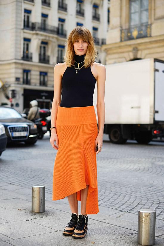 Девушка в оранжевой асимметричной юбке, черный топ и кроссовки