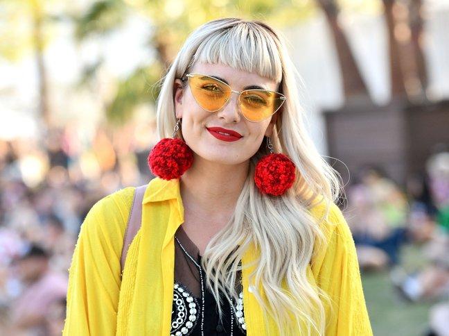 Девушка в прозрачных солнцезащитных очках кошачий глаз, большие красные серьги и желтый кардиган
