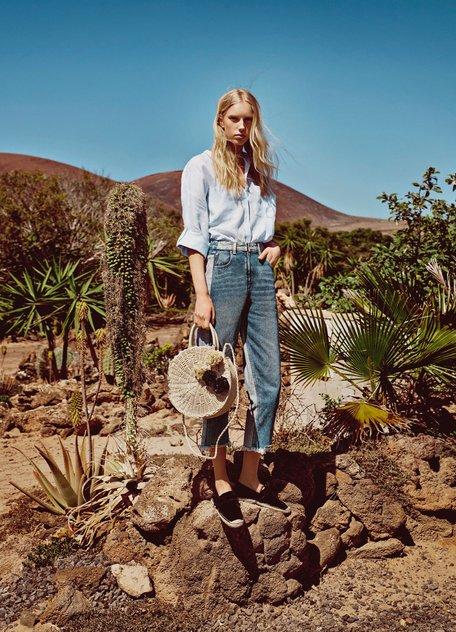 Девушка в укороченных джинсах, голубая футболка и соломенная сумка, стиль бохо