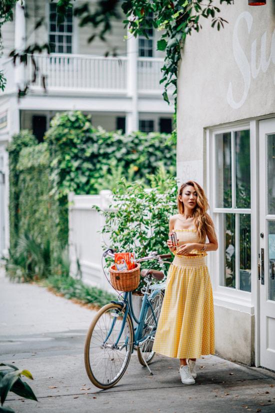 Девушка в желтом космюме в клетку с юбкой миди и кроп топом, белые кеды