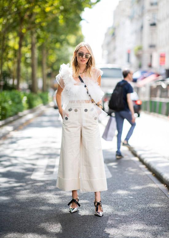 Девушка в белых широких брюках и кружевной блузке