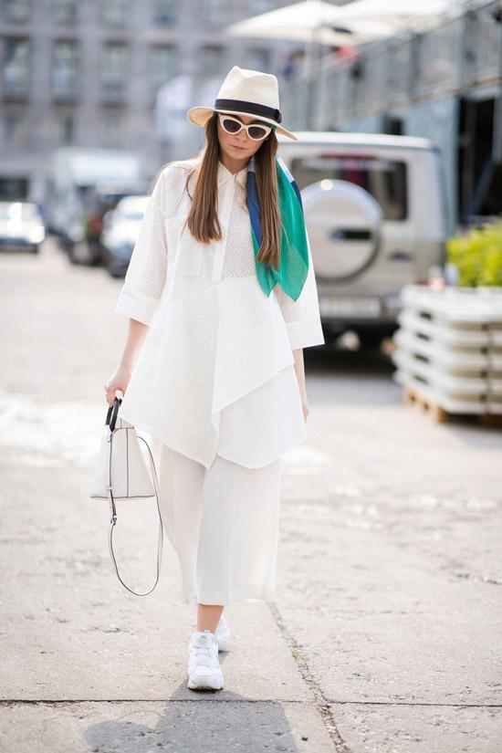 Девушка в белых широких брюках и удлиненной рубашке оверсайз