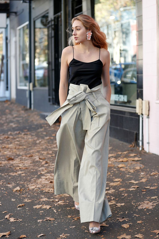 Девушка в брюках палаццо и черном топе