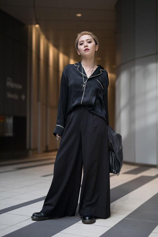 Девушка в черных брюках палаццо и рубашка в пижамном стиле