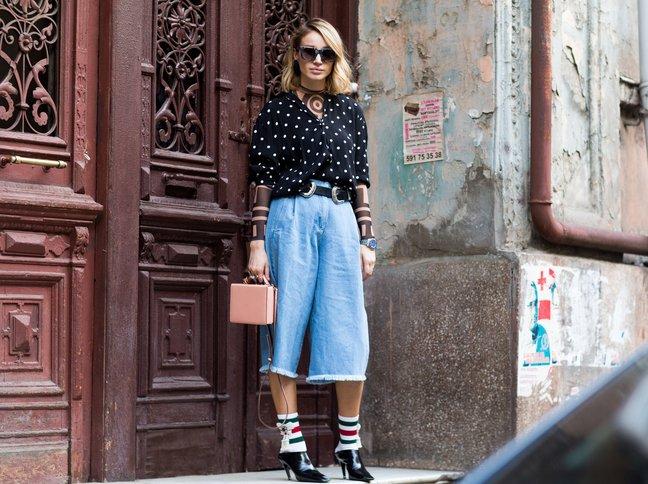 Девушка в джинсовых брюках кулотах и черной блузке с длинными рукавами