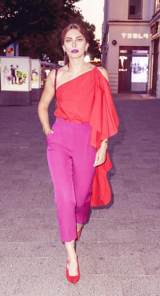 Девушка в елегантных укороченныю брюках и красном топе на одно плечо