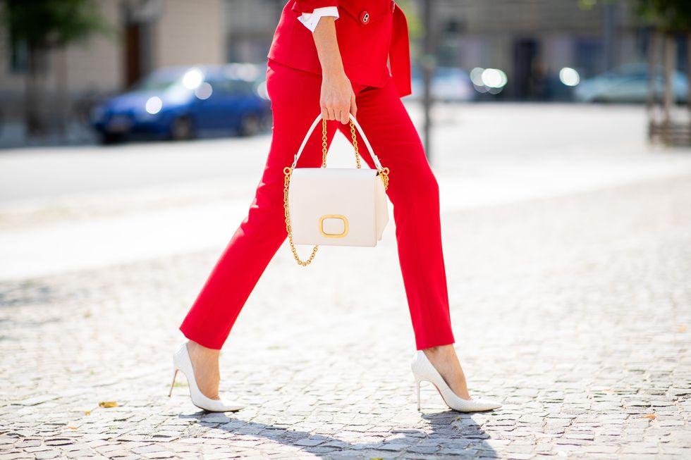 Девушка в красном костюме с элегантными брюками и белые туфли и сумочка
