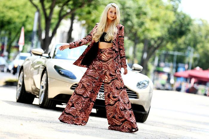 Девушка в пестрых брюках палаццо с принтом, пиджак и черный кроп топ