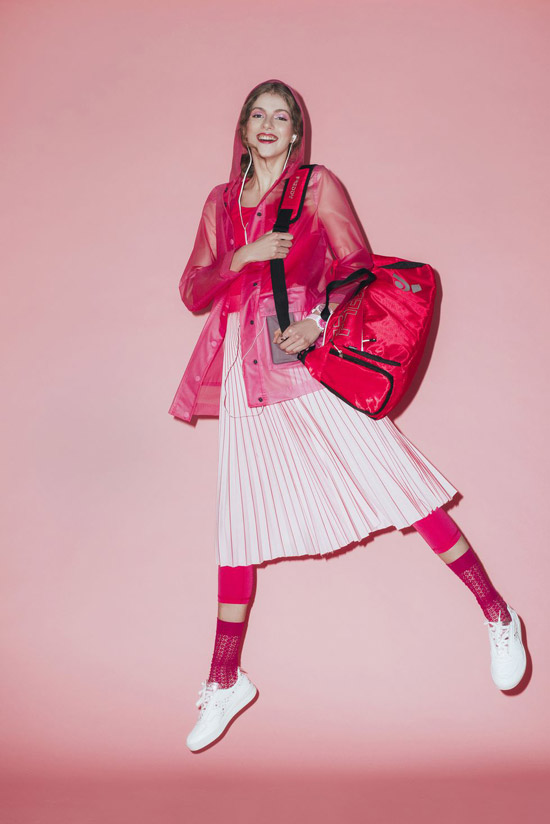 Девушка в плиссированной юбке миди, яркая куртка и спортивная сумка