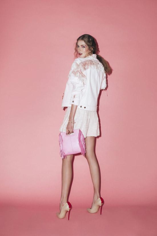 Модель в розовой мини юбке и джинсовая куртка с бахромой и туфли на шпильке