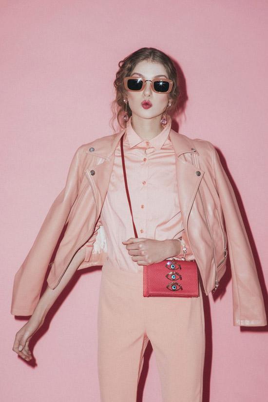 Модель в розовых брюках, рубашка и кожаная куртка, кораловая сумка