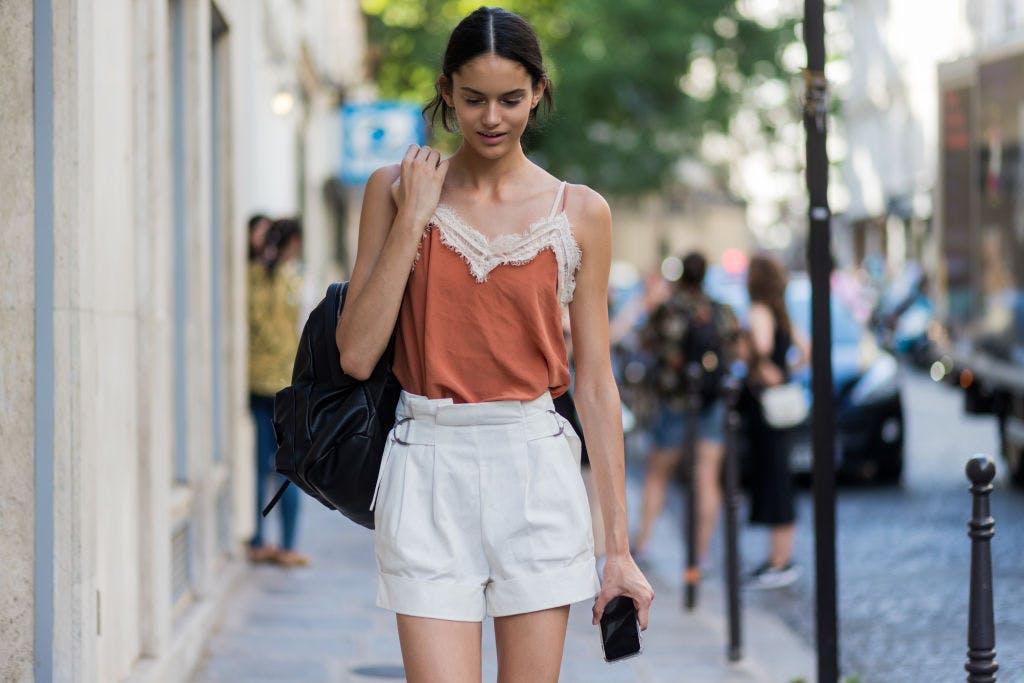 Девушка в белых шортах с высокой талией и оранжевый топ
