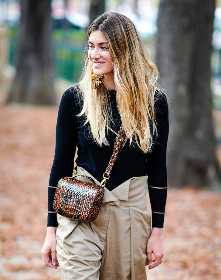 Девушка в бежевых брюках палаццо, черная водолазка и мини сумочка из змеиной кожи