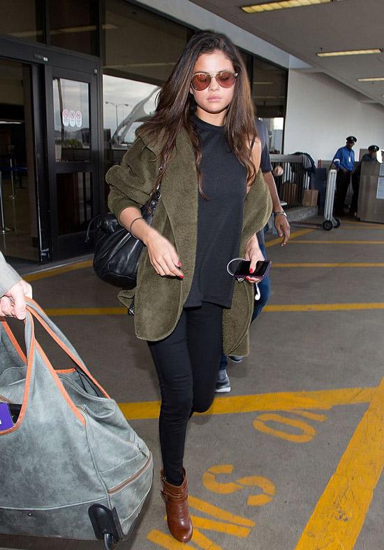 Девушка в черных лосинах и футболке, зеленый пиджак из бархата и коричневые ботильоны