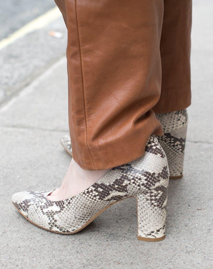 Девушка в коричневых брюках и туфлях из змеиной кожи