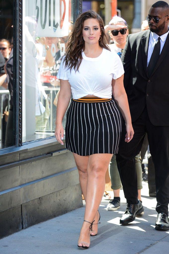 Девушка в мини юбке в полоску и белая футболка