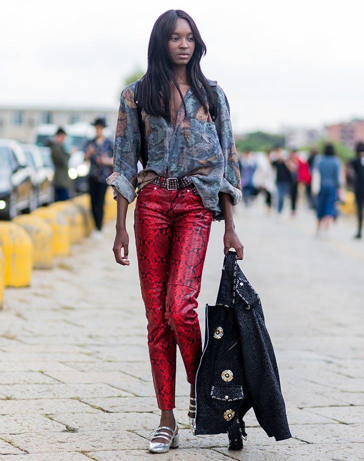 Девушка в рубашке и красных брюках со змеиным принтом