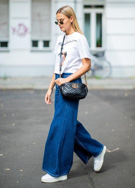 Девушка в широких синих джинсах и белой футболке, черная сумочка