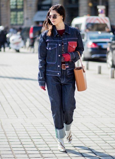 Девушка в темно синих джинсах с отворотом, синяя куртка из денима и белые сапоги