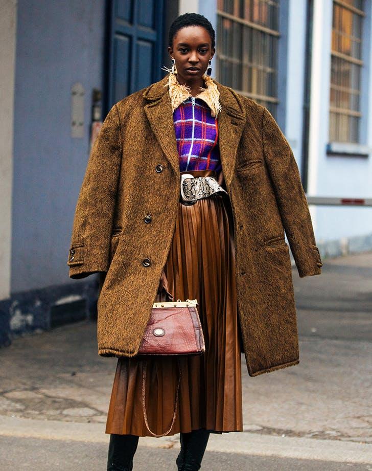 Девушка в юбке миди, коричневое пальто и ремень из змеиной кожи