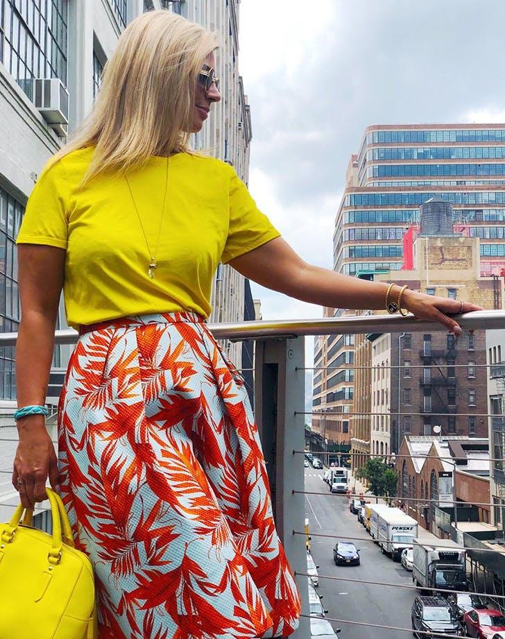 Девушка в желтой футболке и юбке миди с ярким принтом