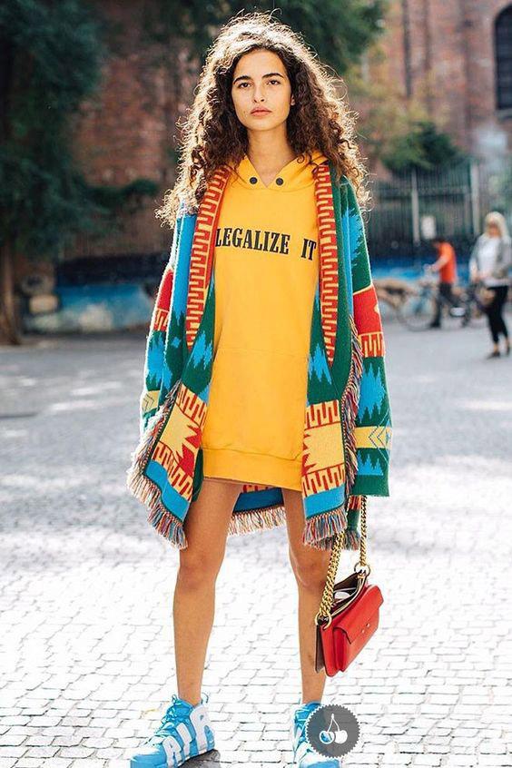 Девушка в желтой худи с капюшоном и голубые-кроссовки