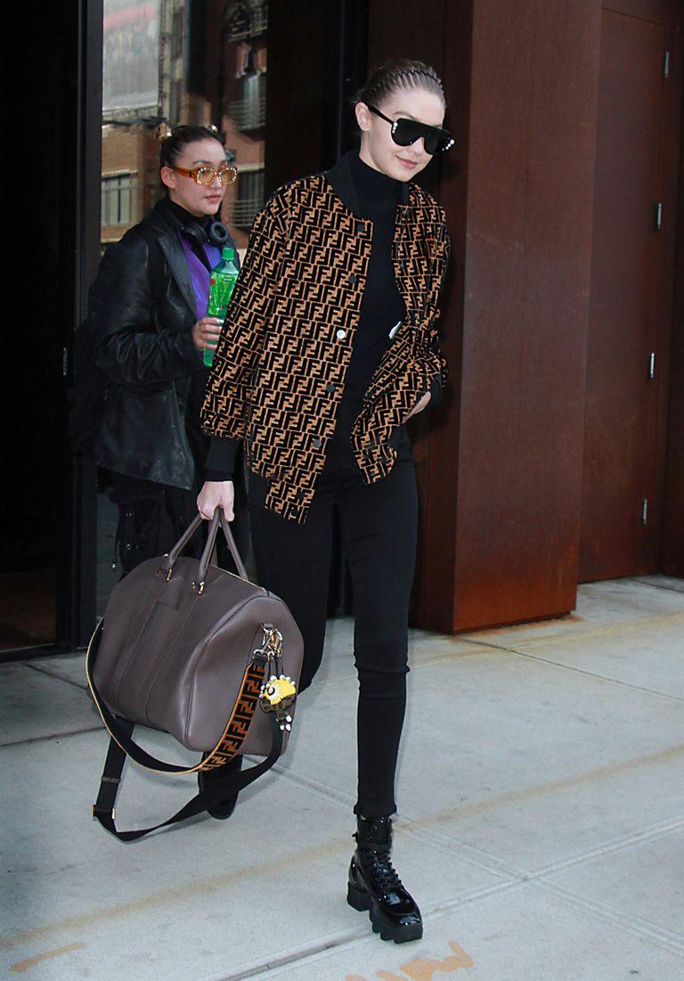Джиджи Хадид в черных лосинах, дизайнерская куртка и большая сумка