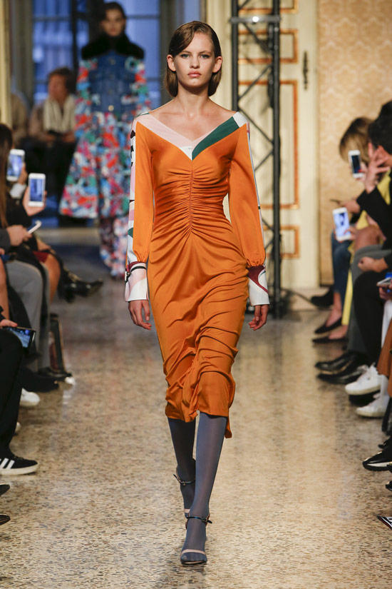 Модель в атласном оранжевом платье с длиными рукавами от Emilio Pucci