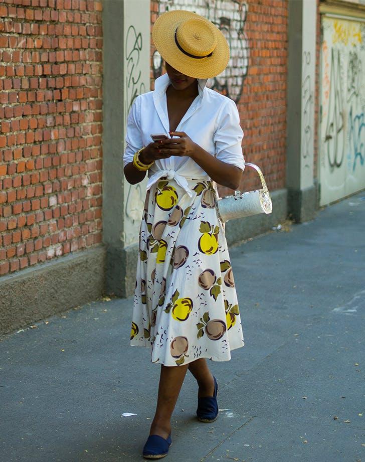 Модель в белой рубашке и юбке миди, соломенная шляпа