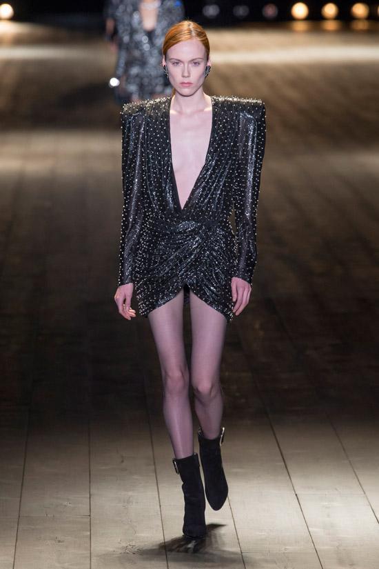 Модель в черном мини платье с объемными плечами и глубоким декольте от Saint Laurent