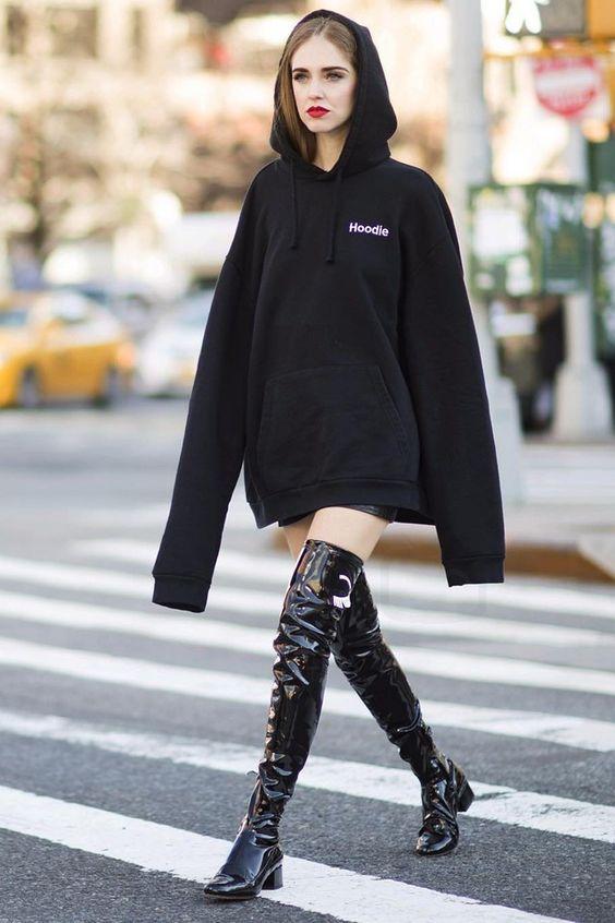 Модель в черной толстовке с капюшоном и черных лаковых ботфортах