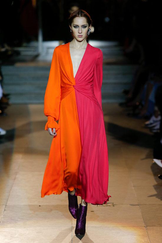 Модель в красно оранжевом платье с длинными рукавами от Carolina Herrera