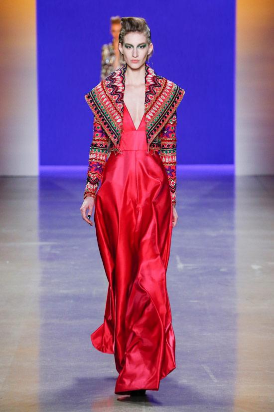 Модель в красном атласном плтье макси и пестрой кофте от NaeemтKhan