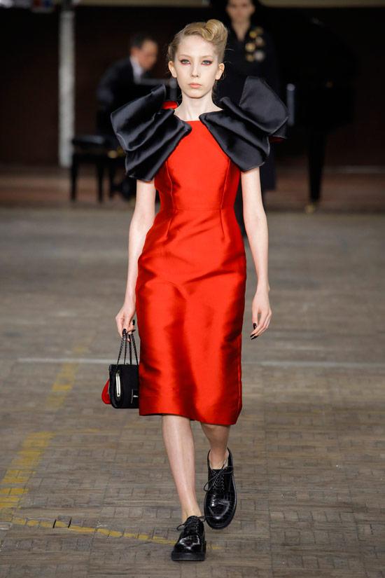 Модель в прямом красном платье с объемными плечами от Antonio Marras