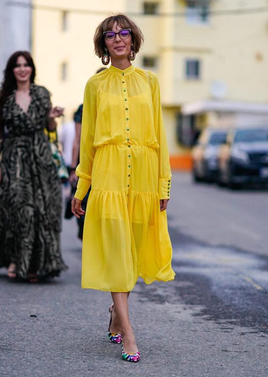 Модель в рком желтом платье миди и разноцветных туфлях